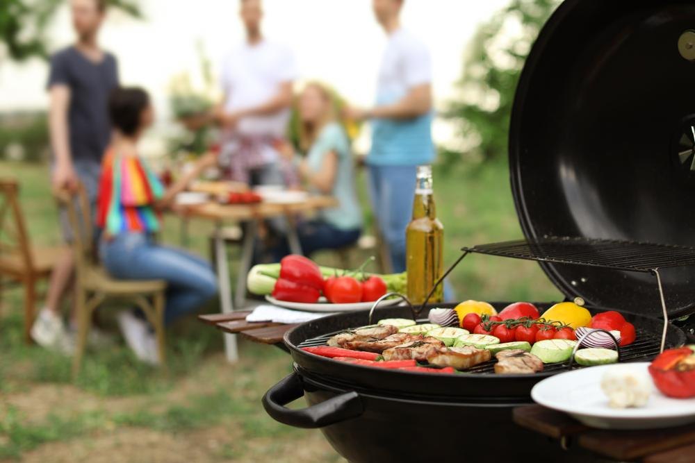 A grill with meat and vegetables cooking, with a small gathering of people at a picnic table in the background.