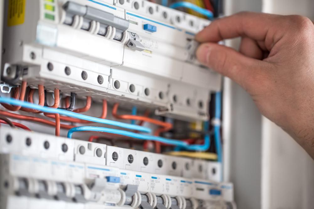 A person checking a fuse box