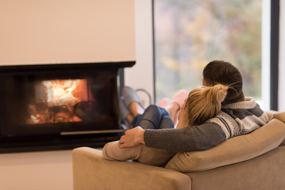 A young couple in winter attire sitting on couch in living room in front of fireplace