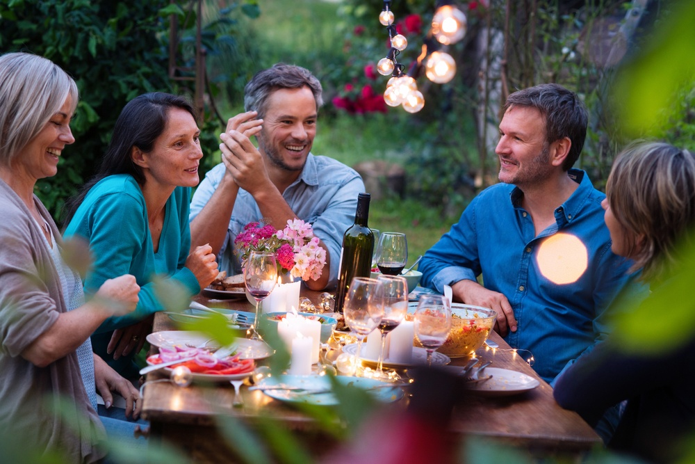 A group of adults sitting at a table in a well-lit backyard during the evening